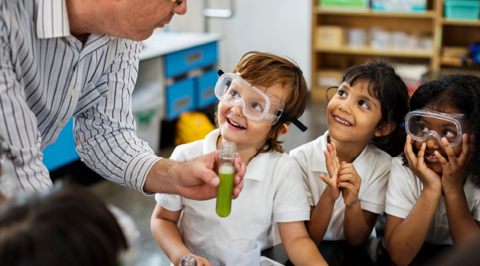 Children smiling at a science teacher